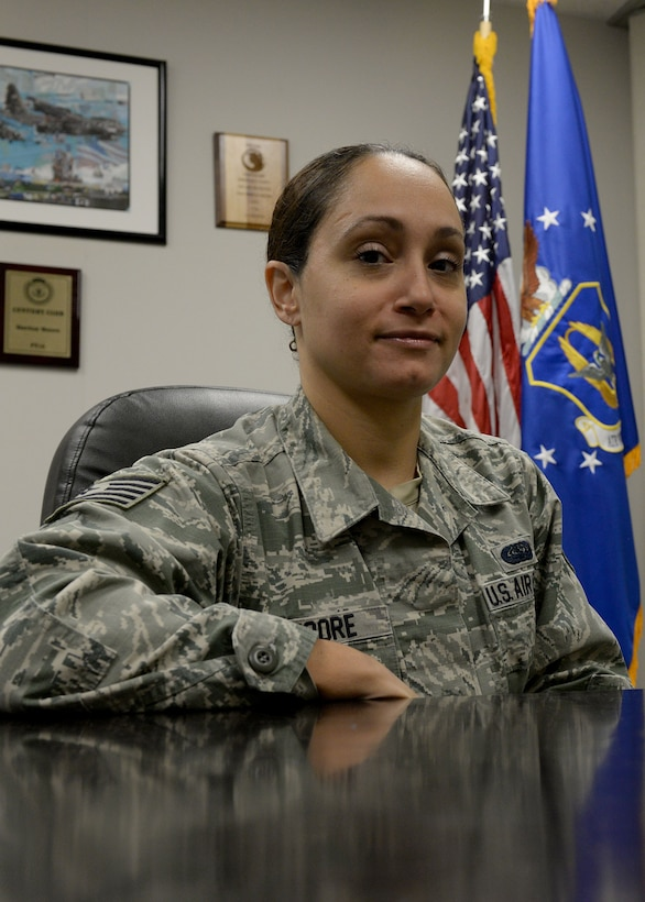 A woman in the Air Force Battle Uniform sits at a desk and smiles at the camera with an American Flag and the Reserve flag behind her.