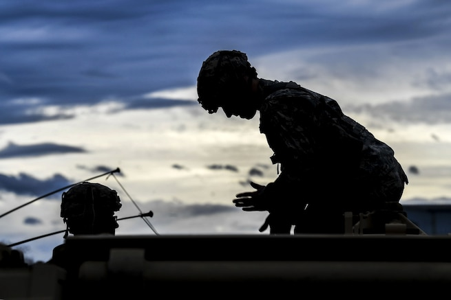 A soldier, shown in silhouette, leans over and motions while working on a weapon system with another soldier.
