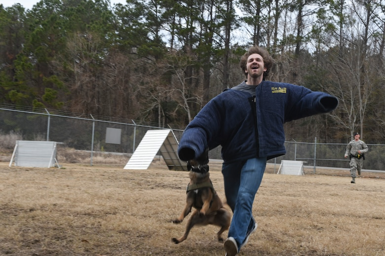 Mike Krieg, South Carolina Stingrays defensemen, participates in a military working dog demonstration with Staff Sgt. Joshua Plucinski, 628th Security Forces Squadron MWD handler at the MWD building, Jan. 10, 2018.