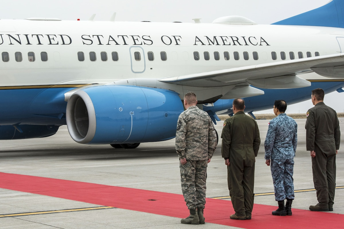 Four service members stand in a row by a red carpet and an aircraft on a flightline.
