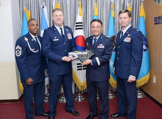 "U.S. Air Force Col. David Shoemaker, 8th Fighter Wing commander, presents Republic of Korea Col. Jun-sun Cha, outgoing 38th Fighter Group commander ""Thor"", with a parting gift following the change of command ceremony at Kunsan Air Base, RoK, Jan. 17, 2018.  Cha recognized the 8th FW in his farewell speech noting that ""we are one team,"" and the partnership between the two groups is something he will remember most. (Courtesy photo)"
