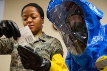 Airman 1st Class Briana McIver, left, 23d Aerospace Medicine Squadron (AMDS) bioenvironmental engineering apprentice, and 2nd Lt. Eric Olson, 23d AMDS bioenvironmental engineer, read instructions for a hand held assay (HHA) during biohazard readiness training, Jan. 12, 2018, at Moody Air Force Base, Ga. A HHA distinguishes whether or not the sample is a deadly protein. This process of going through the instructions ensures standardization of sampling. The Bioenvironmental Engineering Flight tested their response capabilities in a simulated contamination scenario. Bioenvironmental engineering specialists focus on reducing health hazards in the workplace and surrounding areas. (U.S. Air Force photo by Airman 1st Class Erick Requadt)