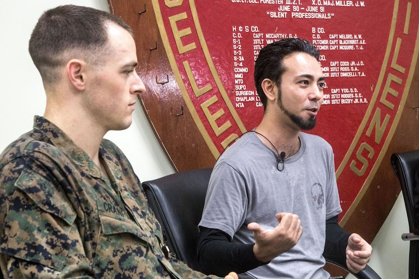 A Marine and a civilian sit together on a stage.