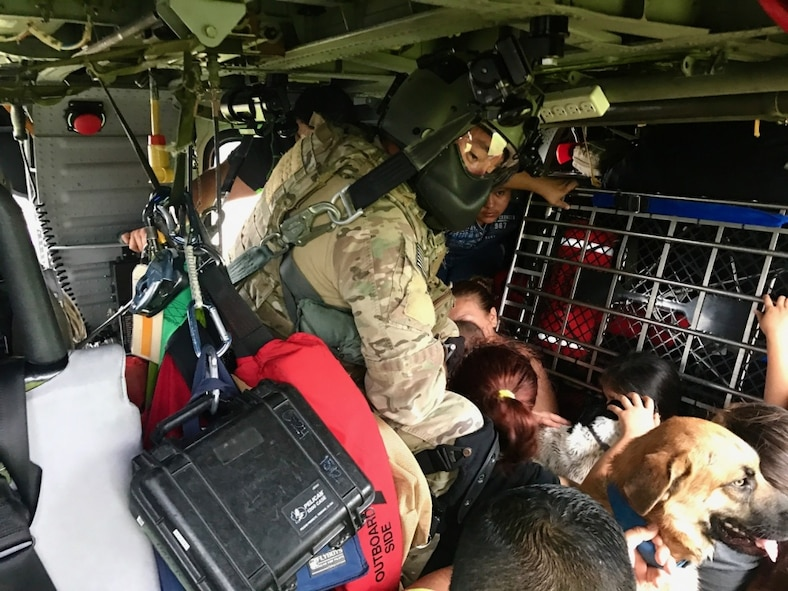 Senior Airman Davy Brinkmann, 920th Rescue Wing, Patrick Air Force Base, Florida, special missions aviations specialist, gets sight on a fellow pararescuemen below as they prepare to hoist two stranded victims of Hurricane Harvey Aug. 31, 2017 from Beaumont, Texas.