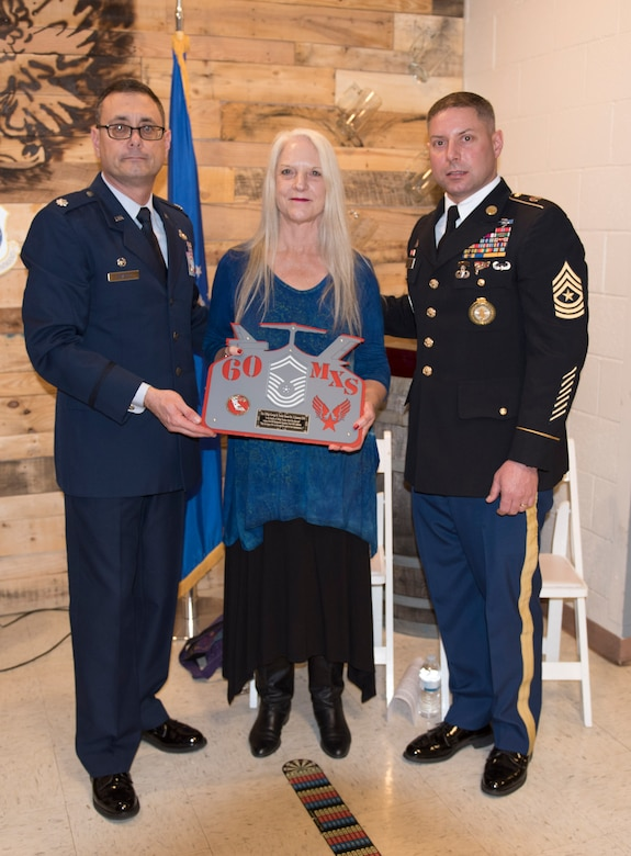 Lt. Col. Claudio Covacci, 60th MXS commander(left), Michelle Marinucci, daughter of late Chief Master Sgt. George R. Tucker(center), and James Marinucci, grandson of late Chief Master Sgt. George R. Tucker(right), stand with a plackard the 60th Maintenance Squadron presented to Tucker's family in tribute to the work he accomplished for the squadron while he was alive January 12 at Travis Air Force Base, Calif. Tucker worked at Travis from 1964 until his retirement in 1985.