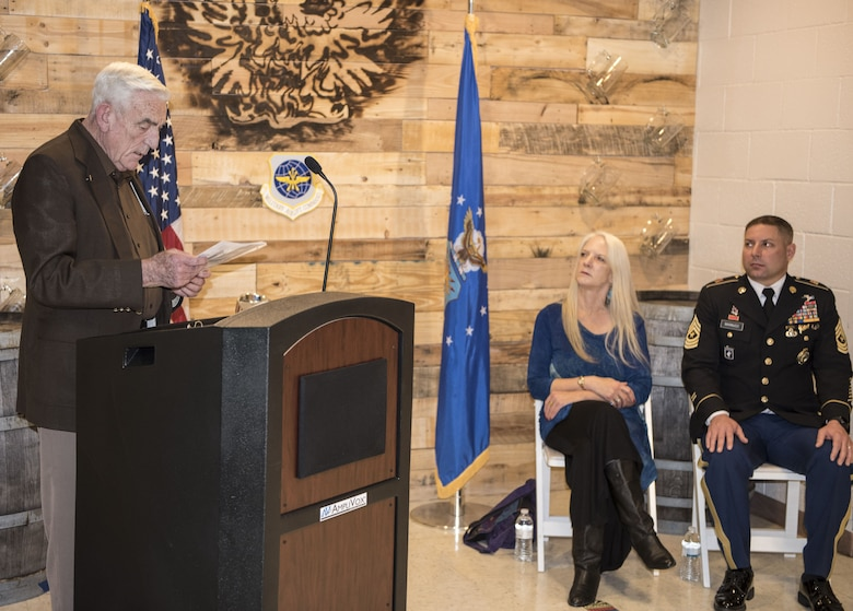 "Retired Chief Master Sgt. James ""Andy"" Anderson(left) makes a speech about late Chief Master Sgt. George R. Tucker while his family, Michelle Marinucci, daughter of Tucker(center), and James Marinucci, grandson of Tucker(right) look on. Both Anderson and Tucker were assigned to Travis in 1964 and spent many years working together.(U.S. Air Force photo by Airman 1st Class Christian Conrad/Released)"