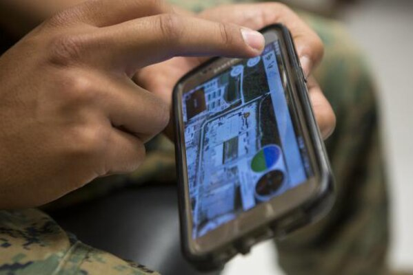 A Marine uses a new app that helps to find people and groups in a new and unfamiliar area.
