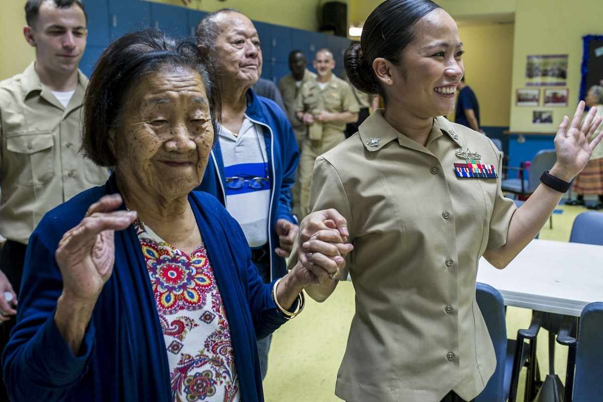 A sailor holds hands with an elderly woman, as they both smile and raise their hands.