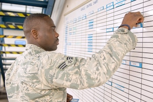 An airman places a piece of paper on a white board.