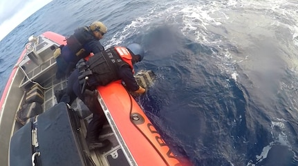 Coast Guard boat crew pulls bales of cocaine from the water