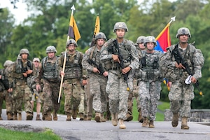 A group of military cadets march with weapons and gear.