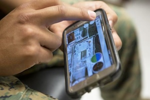 A Marine uses a new application on a phone.