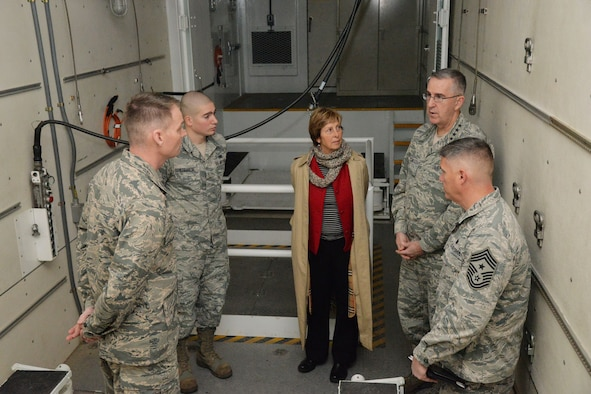 U.S. Air Force Gen. John Hyten, commander of U.S. Strategic Command (USSTRATCOM); his wife Laura; and Chief Master Sgt. Patrick McMahon, senior enlisted leader of USSTRATCOM, speak with Col. David Miller, 341st Maintenance Group commander, and Senior Airman Richard Straniere, 341st Maintenance Group maintainer, while touring a payload transporter in the maintenance bay at Malmstrom Air Force Base, Mont., Jan. 16, 2018.