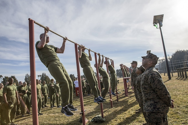 A row of Marines do pullups as fellow Marines observe.