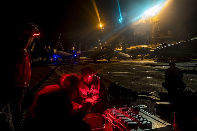 Sailors, illuminated by red light, work while sitting a ship's flight deck in darkness.