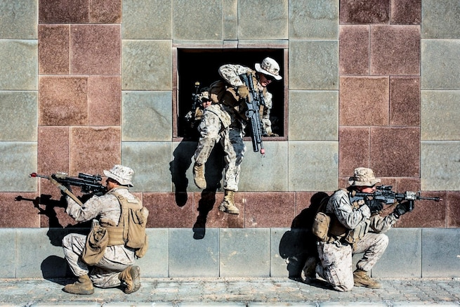 A Marine jumps through a building opening as two Marines kneel and point weapons outside it.