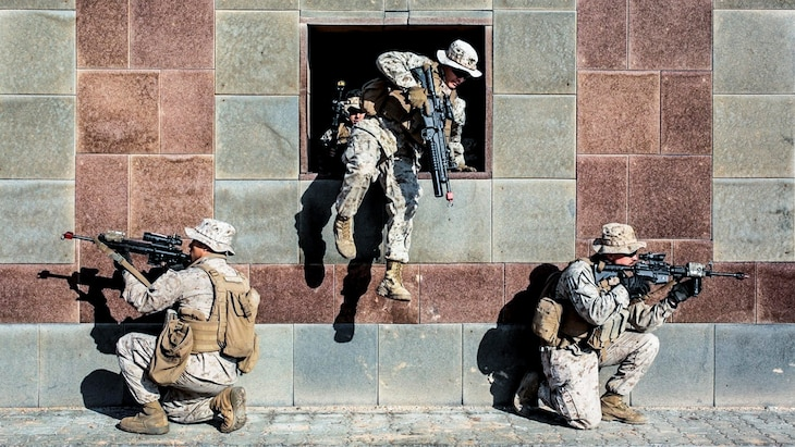 A Marine jumps through a building opening as two Marines kneel and point weapons outside.