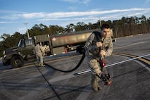 Airman 1st Class Evan Valance, 23d Logistics Readiness Squadron fuels distribution operator, drags a fuel hose away from an M-11 refueling truck to conduct HH-60G Pave Hawk hot-pit refueling operations, Jan. 16, 2018 at Moody Air Force Base, Ga. Airmen who work in the petroleum, oils and lubricants (POL) flight frequently use hot pit refueling, which is a more efficient tactic that allows aircrews a quick transition from the flight line back to their current objective. (U.S. Air Force photo by Senior Airman Daniel Snider)