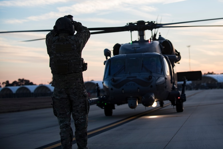 A special missions aviator assigned to the 41st Rescue Squadron directs an HH-60G Pave Hawk to a refueling point for hot-pit refueling operations, Jan. 16, 2018 at Moody Air Force Base, Ga. Airmen who work in the petroleum, oils and lubricants (POL) flight frequently use hot pit refueling, which is a more efficient tactic that allows aircrews a quick transition from the flight line back to their current objective. (U.S. Air Force photo by Senior Airman Daniel Snider)