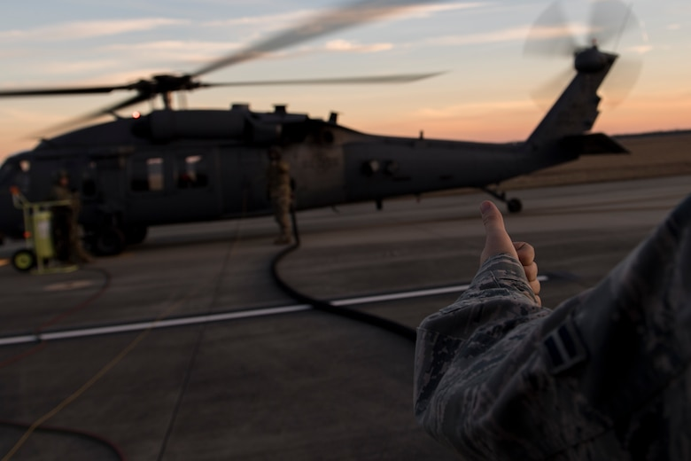 Airman 1st Class Evan Valance, 23d Logistics Readiness Squadron fuels distribution operator, communicates with a special missions aviator assigned to the 41st Rescue Squadron during HH-60G Pave Hawk hot-pit refueling operations, Jan. 16, 2018 at Moody Air Force Base, Ga. Airmen who work in the petroleum, oils and lubricants (POL) flight frequently use hot pit refueling, which is a more efficient tactic that allows aircrews a quick transition from the flight line back to their current objective. (U.S. Air Force photo by Senior Airman Daniel Snider)