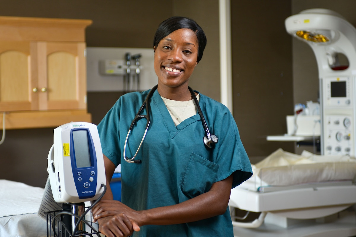 A woman poses for a photo next to medical equipment.
