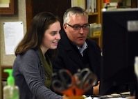 Emily Copeland, 325th Force Support Squadron's new librarian, and Mark Rix, 325th Force Support Squadron Force Development flight chief, process data on Copeland's computer at Tyndall Air Force Base, Fla., Jan. 18, 2018. As the new librarian, Copeland will wear many hats: facility manager, resource manager, information technology equipment custodian and activities director. The Tyndall library supports the community by providing education, reference and reading materials for Airmen and family members of all ages. (U.S. Air Force photo by Airman 1st Class Isaiah J. Soliz/Released)