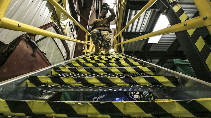 A soldier, shown from the bottom of stairway, walks down its yellow and black striped metal steps.