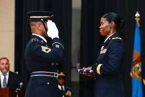 A soldier salutes another soldier holding a flag.