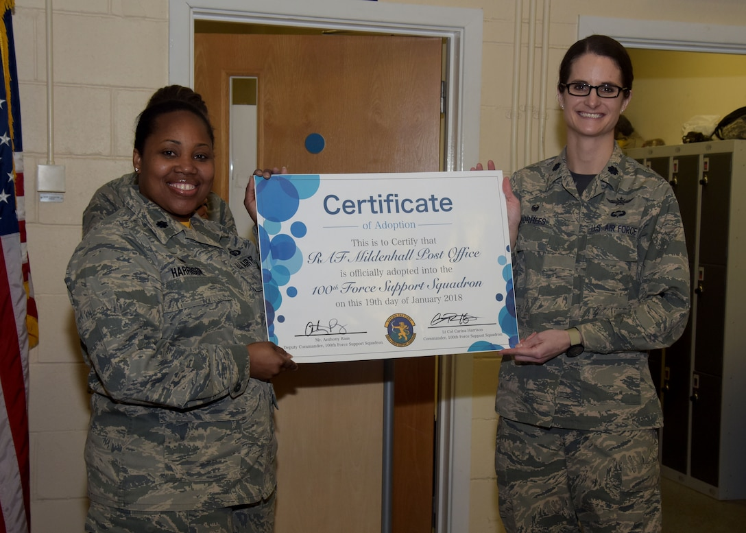 U.S. Air Force Lt. Col. Carina Harrison, 100th Force Support Squadron commander, and Lt. Col. Stacie Voorhees, 100th Communications Squadron commander, hold a certificate designating the post office as a flight of the 100th FSS at RAF Mildenhall, England Jan. 19, 2018. The reclassification brings mission support agencies into the same squadron. (U.S. Air Force photo by Senior Airman Justine Rho)