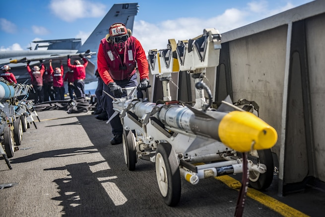 A sailor in a red uniform pushes a yellow-tipped missile on a wheeled cart on a ship's flight deck.