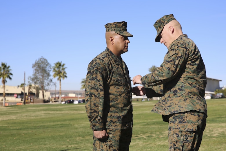 Sgt. Maj. Michael E. Cedeno, off going sergeant major, 1st Battalion, 7th Marine Regiment, Marine Corps Air Ground Combat Center Twentynine Palms, Calif., receives the meritorious service medal for outstanding service for 1/7 during the post and relief ceremony at the commanding general's lawn aboard the Ground Combat Center Jan. 11, 2018. During the ceremony Cedeno relinquished his post as sergeant major to Sgt. Maj. Brian E. Anderson, incoming sergeant major, 1/7, MCGACC. (Official Marine Corps photo by Lance Cpl. Margaret Gale)
