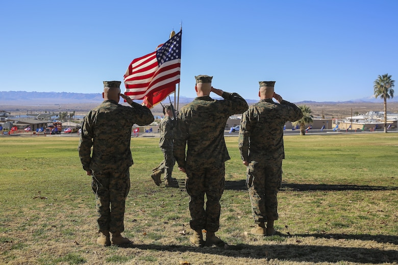 Sgt. Maj. Michael E. Cedeno, off going sergeant major, 1st Battalion, 7th Marine Regiment, Marine Corps Air Ground Combat Center Twentynine Palms, Calif., Sgt. Maj. Brian E. Anderson, incoming sergeant major, 1/7, MCAGGC, and Lt. Col. Erick T. Clark, commanding officer, 1/7, MCAGCC, salute the colors during the pass and review during the post and relief ceremony at the commanding generals lawn aboard the Combat Center, Jan. 11, 2018. During the ceremony Cedeno relinquished his post as sergeant major to Anderson. (Official Marine Corps photo by Lance Cpl. Margaret Gale)