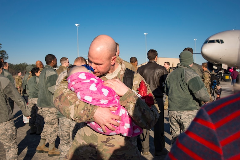 Tech. Sgt. Travis Van Haren, 74th Aircraft Maintenance Unit weapons expediter, kisses his baby during a redeployment ceremony, Jan. 19, 2018, at Moody Air Force Base, Ga. The 74th Fighter Squadron conducted around-the-clock planning and operations, which have decimated ISIS' fighting capacity with precise strikes, erasing tens of thousands of fighters from ISIS rosters. (U.S. Air Force photo by Andrea Jenkins)