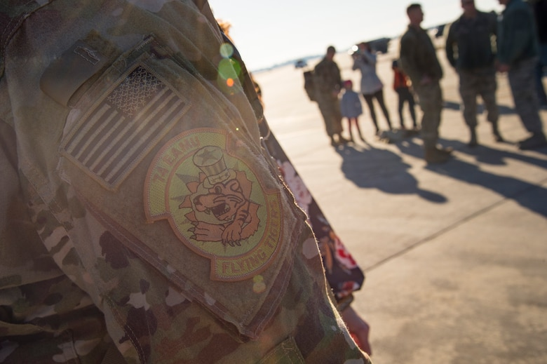 A 74th Expeditionary Aircraft Maintenance Unit patch rests on the arm of a returning maintainer during a redeployment ceremony for the 74th Fighter Squadron, Jan. 19, 2018, at Moody Air Force Base, Ga. The 74th FS conducted around-the-clock planning and operations, which have decimated ISIS' fighting capacity with precise strikes, erasing tens of thousands of fighters from ISIS rosters. (U.S. Air Force photo by Andrea Jenkins)