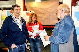 Moe Adams (center), resident engineer at the Emergency Field Office in Redwood Valley, and Norbert Suter (left), chief of Operations Section at the Sonoma Recovery Field Office, spoke with a resident during the Mendocino County Community meeting on Jan. 17.