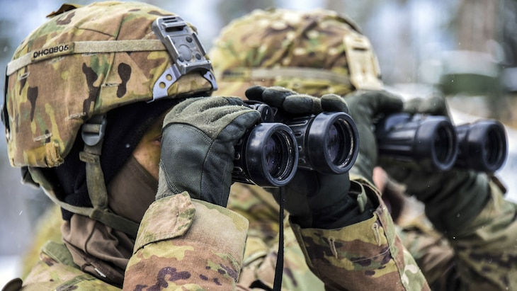 Two soldiers look through binoculars.