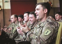 The Soldiers of the 5th Squadron, 4th Cavalry Regiment, 2nd Armored Brigade Combat Team, 1st Infantry Division give a round of applause after listening to a holiday concert performed by a group of Polish students in Swietoszow, Poland on Dec. 22.