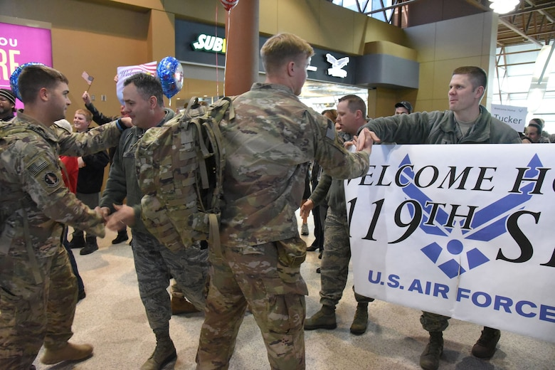 1st Lt. Jason Augdahl, the 119th Security Forces Squadron commander, and Chief Master Sgt. Steve Gibson welcome their people home from deployment.