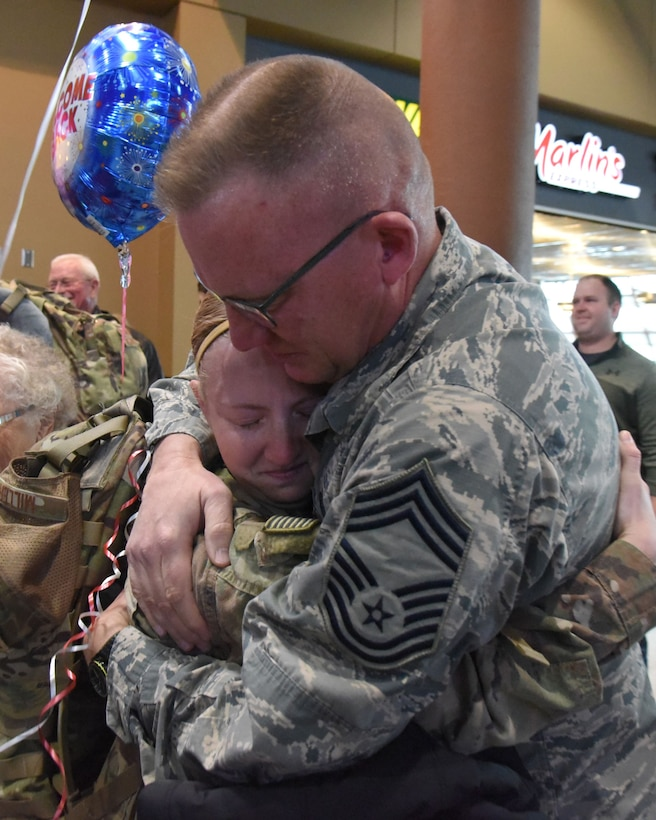 Chief Master Sgt. Jeff Miller hugs his daughter Tech. Sgt. Elizabeth Miller, of the 119th Security Forces Squadron, North Dakota Air National Guard, as she returns from deployment.