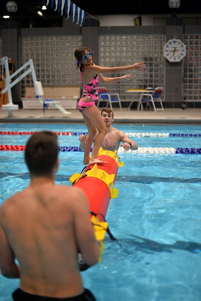 Trinity Hopwood attempts to maintain balance on a synthetic log with the assistance of two lifeguards at the base pool located inside the Offutt Field House on Jan. 13, 2018.