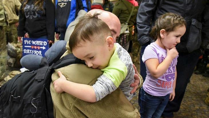 A boy, with closed eyes and a slight smile, tightly hugs his dad, who is kneeling to the boy's height and returning the embrace.