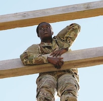 """Pfc. Yaa Agyemang, financial clerk, 9th Financial Management Sustainment Unit, 1st Infantry Division Sustainment Brigade, maneuvers through the """"confidence climb"""" on the air assault confidence course during the 2017 Special Troops Battalion, Sustainment Brigade Soldier of the Year competition Nov. 15, 2017, at Fort Riley."""