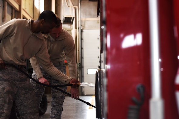 Senior Airman Micah Adams, 47th Civil Engineer Squadron fire department firefighter and Airman 1st Class Ian Miners, 47th CES firefighter, sprays off and scrubs a fire truck wheel in the fire department at Laughlin Air Force Base, Texas, Jan. 18, 2018. According to Adams, keeping the firehouse clean is important, and—after studying and training—remaining ever-prepared is a continual priority. (U.S. Air Force photo/Airman 1st Class Anne McCready)