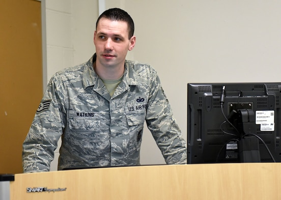 Staff Sgt. Daniel Watkins, 627th Security Forces Squadron unit training manager, stands at a podium while teaching an Expeditionary Active Shooter class at the 627th SFS, Jan. 18, 2018 at Joint Base Lewis-McChord, Wash. Watkins was recognized for outstanding Airmanship after escorting an ill, elderly veteran to an out-of-state Veterans Affairs appointment of his own volition, and ensuring the gentleman's continued care. (U.S. Air Force photo by Staff Sgt. Whitney Taylor)