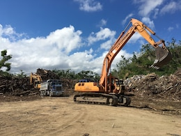 An excavator repositions for operations unloading and loading trucks Nov. 24, 2017, at the Trujillo Alta temporary disposal site in Puerto Rico. Temporary sites serve as municipal collection points for woody debris before it's reduced to mulch or transferred to another location for permanent deposition (mulch recycling site or landfill).