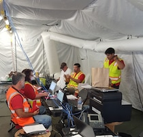 "U.S. Army Corps of Engineers, Walla Walla District, temporary emergency power team members discuss their mission Nov. 25, 2017, in ""the office"" -- a tent at FEMA's Incident Support Base on St. Croix, U.S. Virgin Islands. (left to right) Shawn McCann, quality assurance representative; Mary VanSickle, contract specialist; Rich Hilt, power subject matter expert; Don Redman, mission manager; Carlos Flores Lopez, quality assurance representative."
