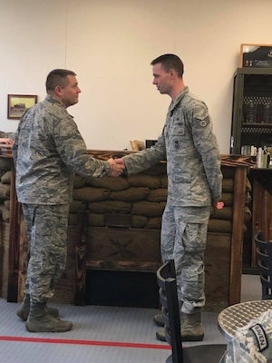 Maj. Michael Holt, 627th Security Forces Squadron commander, presents a coin to Staff Sgt. Daniel Watkins, 627th SFS unit training manager, for outstanding Airmanship, Jan. 12, 2018 at Joint Base Lewis-McChord, Wash. Watkins went above and beyond the call of duty to assist a retired Marine Corps lieutenant colonel, escorting him to an out-of-state Veterans Affairs appointment, and ensuring the gentleman's continued care. (Courtesy photo)