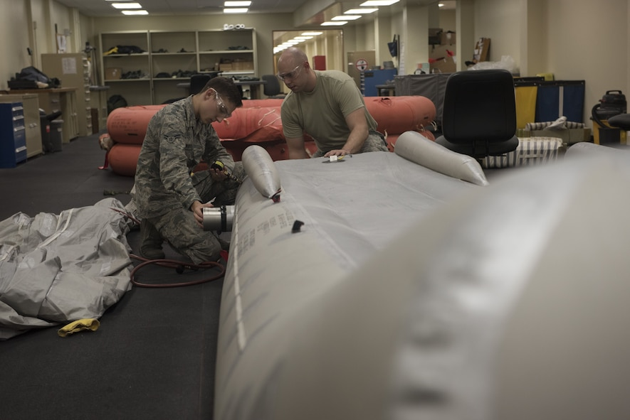 U.S. Air Force Airman 1st Class Joshua Brewer, 18th Operation Support Squadron aircrew flight equipment apprentice, and Staff Sgt. Brandon McDaniels, 18th OSS aircrew flight equipment craftsman, inspect an aircraft slide Jan. 18, 2018, at Kadena Air Base, Japan. AFE Airmen are responsible for inspecting and testing survival equipment for various aircraft on base. (U.S. Air Force photo by Staff Sgt. Micaiah Anthony)