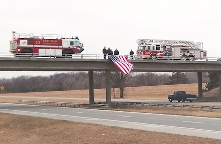 Firefighters from Fort Riley Fire and Emergency Services stand on the overpass of U.S. Interstate 70 near Marshall Army Airfield to honor the funeral procession of Wamego, Kansas, firefighter John Randle Jan. 7 as they travel to his final resting place in Iuka, Kansas. Fort Riley firefighters also served as part of the honor guard during the final call for Randle Jan. 6.