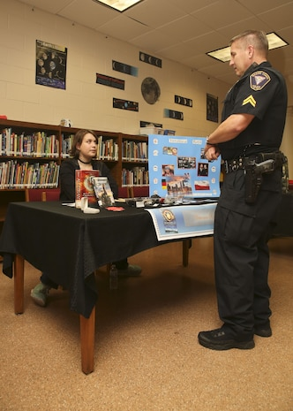 A student displays her presentation to Cpl. Chris Stevens during the Bolden Elementary and Middle School Wax Museum aboard Laurel Bay Jan. 17. Stevens is the School Resource Officer for Laurel Bay schools.